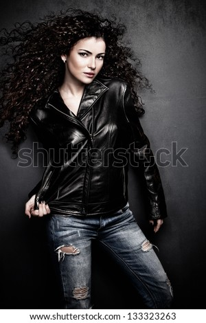 attractive long hair young woman in black leather jacket and blue jeans studio shot small amount of grain added - stock photo