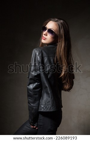 attractive long hair young woman in black leather jacket and pants with sunglasses over dark grey background - stock photo