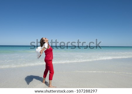 Attractive looking mature woman at beach, enjoying happy life and sunbath, open arms, isolated with sea and blue sky as background and copy space. - stock photo