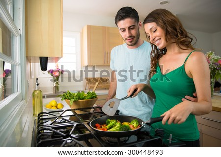 Attractive lovers couple cook together at home vegetables vegan diet health minded - stock photo