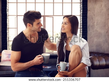 Attractive loving couple drinking tea at home, talking. - stock photo