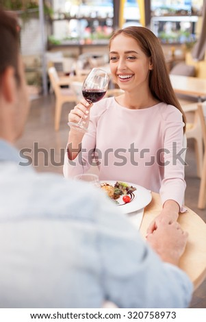 Attractive loving couple is dating in restaurant. They are sitting at the table and flirting. The boyfriend and girlfriend are holding hands. They are drinking wine and laughing - stock photo