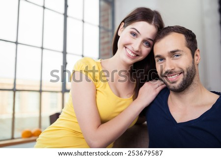 Attractive loving couple posing arm in arm for the camera alongside a large window giving the camera charming warm smiles - stock photo