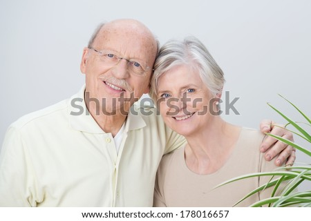 Attractive loving senior couple standing arm in arm with their heads touching enjoying a tender moment together and smiling at the camera - stock photo