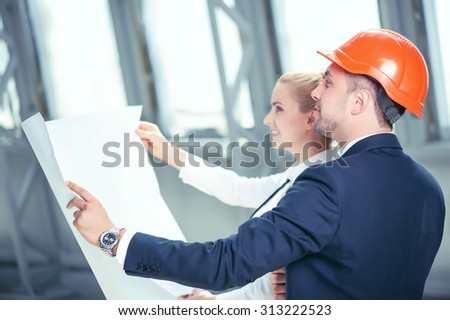 Attractive male architect is explaining the plan of building to his female colleague. They are holding a blueprint and looking at it with aspirations. The man and woman are smiling - stock photo