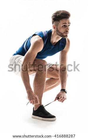 Attractive male athlete is lacing up shoes - stock photo
