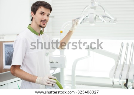 Attractive male dentist is working in lab. He is standing near a medical chair and touching equipment. The man is looking at camera and smiling - stock photo