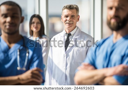 Attractive male doctor in focus of medical group in  hospital. - stock photo