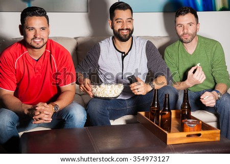 Attractive male Hispanic friends eating popcorn and drinking some beer while watching TV at night - stock photo