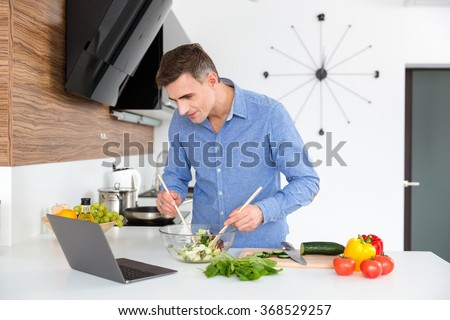 Attractive male in blue shirt looking on the screen of laptop and cooking on the kitchen  - stock photo