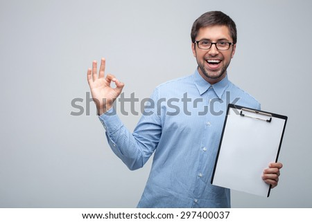 Attractive male manager with eyeglasses is showing okay sign. He is showing a folder of empty papers and smiling. Isolated on grey background and copy space in left side - stock photo