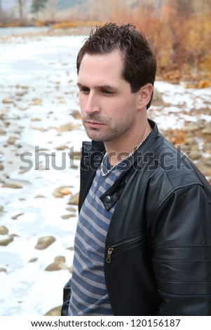 Attractive male outdoors wearing a black leather jacket - stock photo