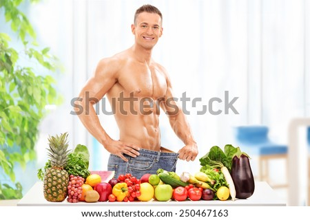 Attractive male posing behind a table with vegetables and fruit at home  - stock photo