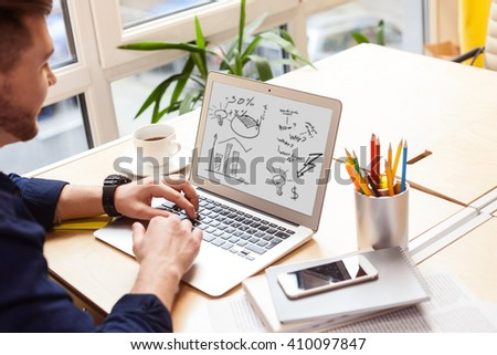 Attractive male student is using a notebook - stock photo