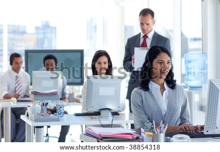 Attractive male supervisor taking notes in a call center - stock photo