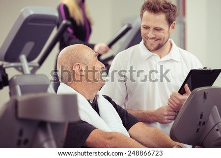 Attractive male trainer in a gym working with a senior man on equipment in a healthy active lifestyle concept - stock photo