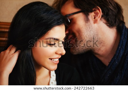 Attractive Male Whispering To His Girlfriend - stock photo