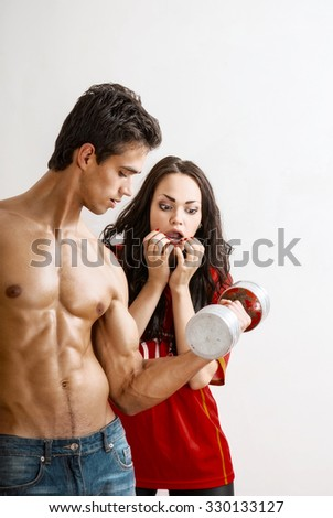 attractive man and woman emotionally train with dumbbells - stock photo