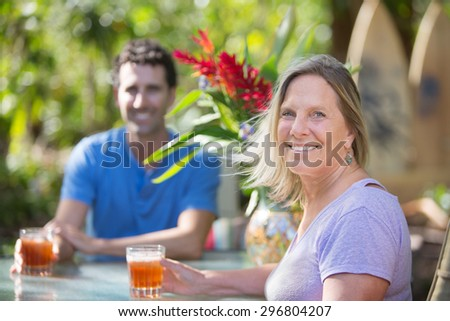 Attractive man and woman on vacation at table - stock photo
