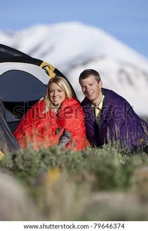Attractive man and woman sitting outside dome tent with mountains in the background. - stock photo