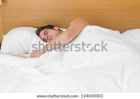 Attractive man asleep in bed in hotel room - stock photo