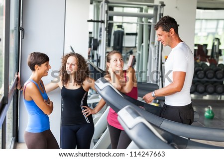 Attractive Man at Gym with Three Women - stock photo
