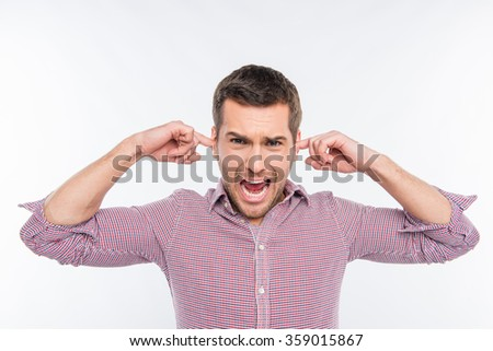 Attractive man clossing his ears and screaming - stock photo