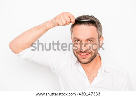 Attractive man combing his hair on white background - stock photo