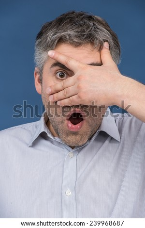 Attractive man covering eyes with his hand. surprised and shocked man looking through hands with one eye - stock photo