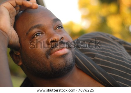 Attractive man daydreaming on a lazy summer afternoon - stock photo