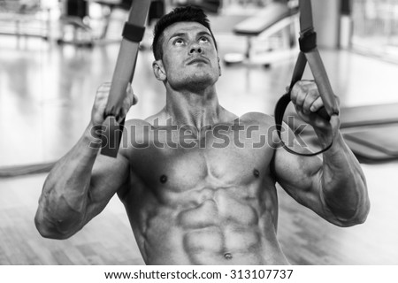 Attractive Man Does Crossfit Push Ups With Trx Fitness Straps In The Gym's Studio - stock photo