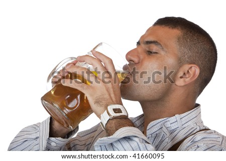 Attractive man dressed in leather trousers (Lederhose) drinks out of Oktoberfest beer stein.  Isolated on white. - stock photo