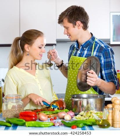 Attractive man helping young wife to prepare healthy dinner - stock photo