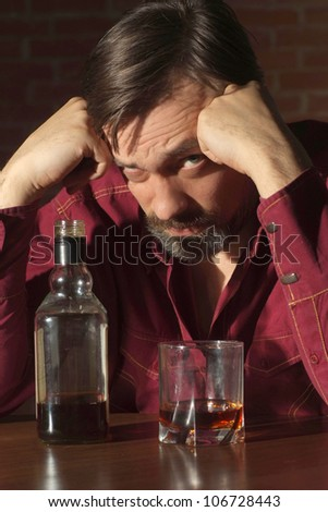 Attractive man in a red shirt with alcohol - stock photo