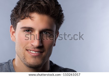 Attractive man in studio with intense eyes looking at camera on a grey background. - stock photo