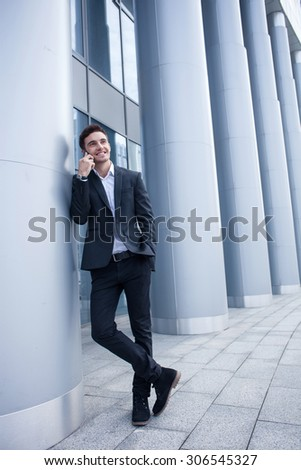 Attractive man in suit is talking on the phone and smiling. He is standing near his office and leaning on the column. The man is putting arm in his pocket. Copy space in right side - stock photo