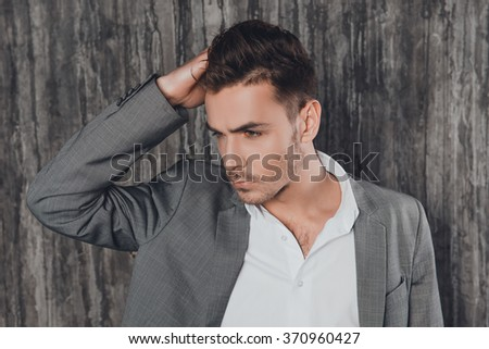 Attractive man in suit on the grey background touching hair - stock photo