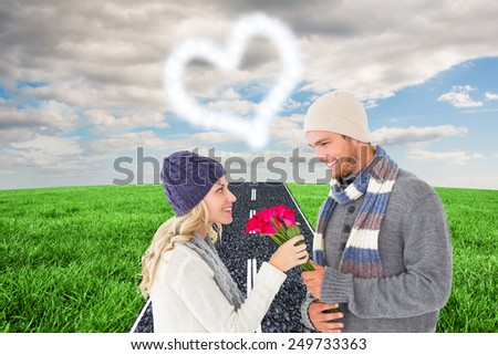 Attractive man in winter fashion offering roses to girlfriend against road on grass - stock photo