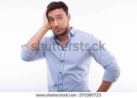 Attractive man is disappointed and hopeless. He has fear for future. He is touching his hand with fright. Isolated on a white background - stock photo