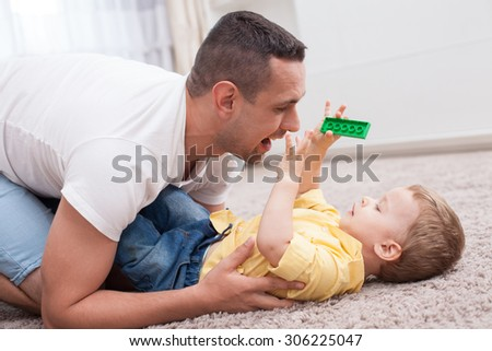Attractive man is playing with his son on flooring. The boy is holding a toy and lying on carpet with joy. His parent is looking at him playfully and smiling - stock photo