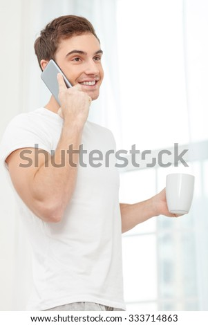 Attractive man is talking on the mobile phone in the morning. He is standing near the window and holding a cup of tea. The man is smiling happily - stock photo