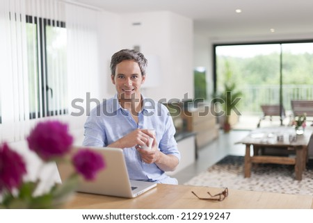 attractive man is using a laptop at home - stock photo