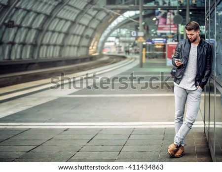 Attractive man is waiting at the train station looking at his smart phone - stock photo