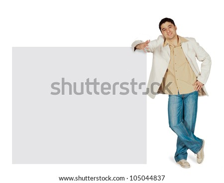 Attractive man leaning to blank gray sign. All on white background. - stock photo