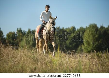 Attractive man on horseback - stock photo