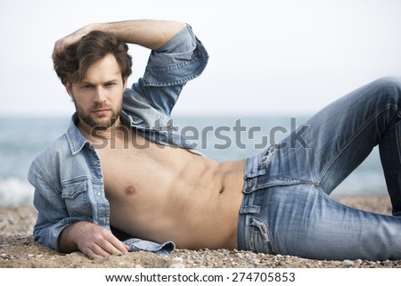 Attractive man on the beach with jeans - stock photo
