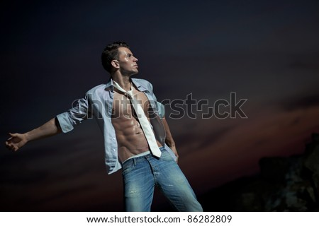 Attractive man over evening sky - stock photo