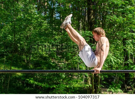 Attractive man pull-ups on a bar in a forest - stock photo