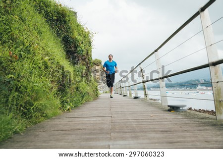 Attractive man running on a wooden walkway next to the sea. Daily training. - stock photo