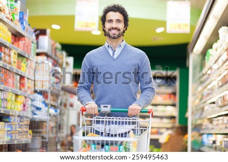 Attractive man shopping in a supermarket - stock photo